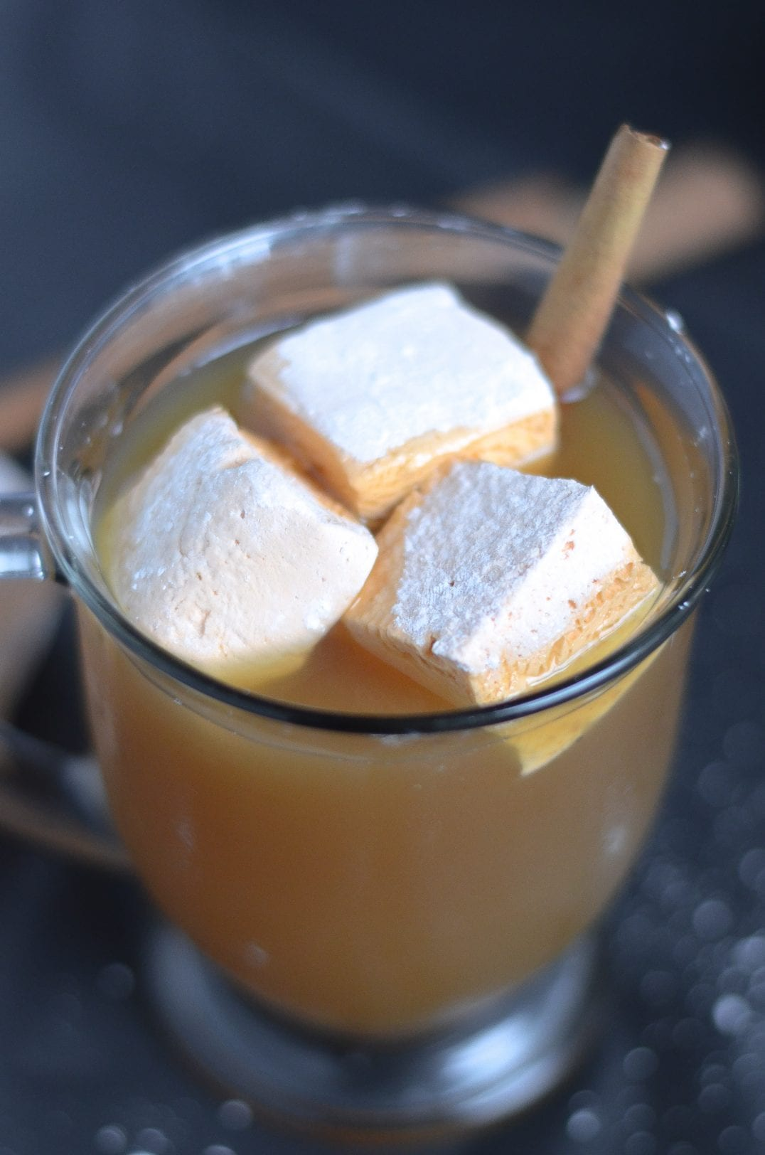 marshmallows sitting in a glass of apple cider