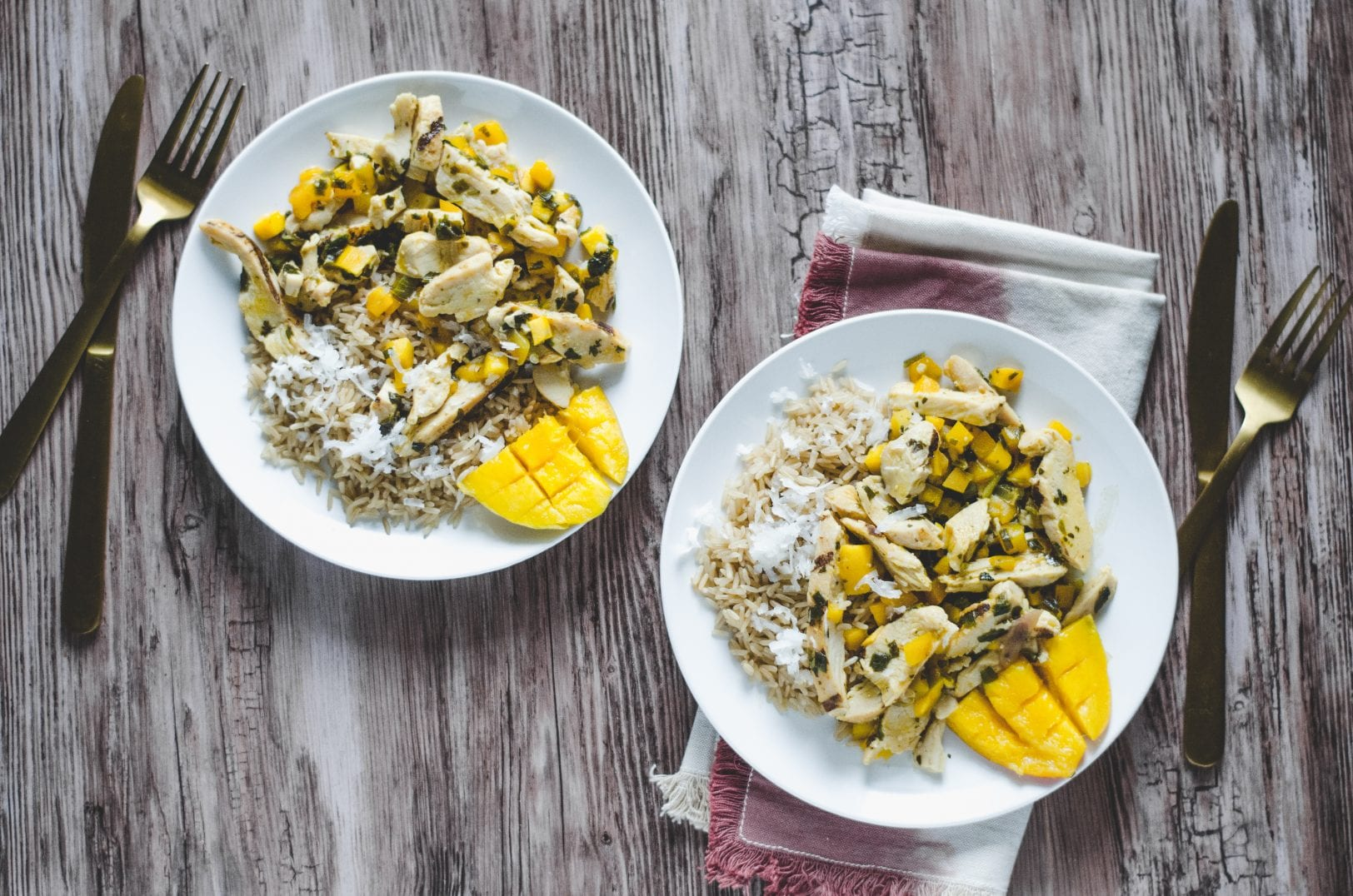mango chicken with coconut rice on two plates