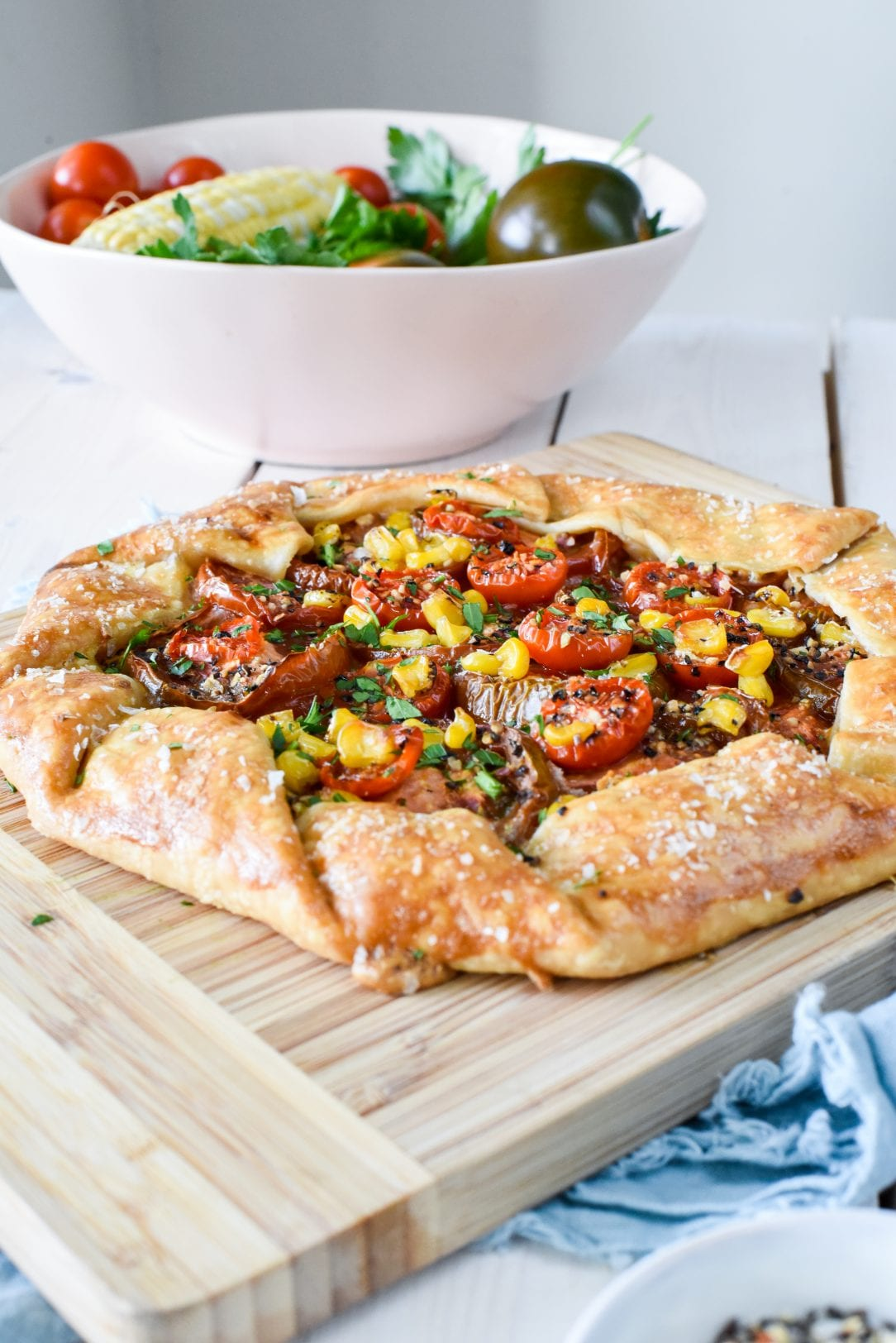 galette with roasted corn and tomatoes sitting on a cutting board