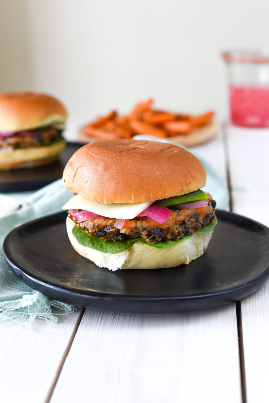 black bean burger with lettuce, cheese, and pickled onion sitting on a plate
