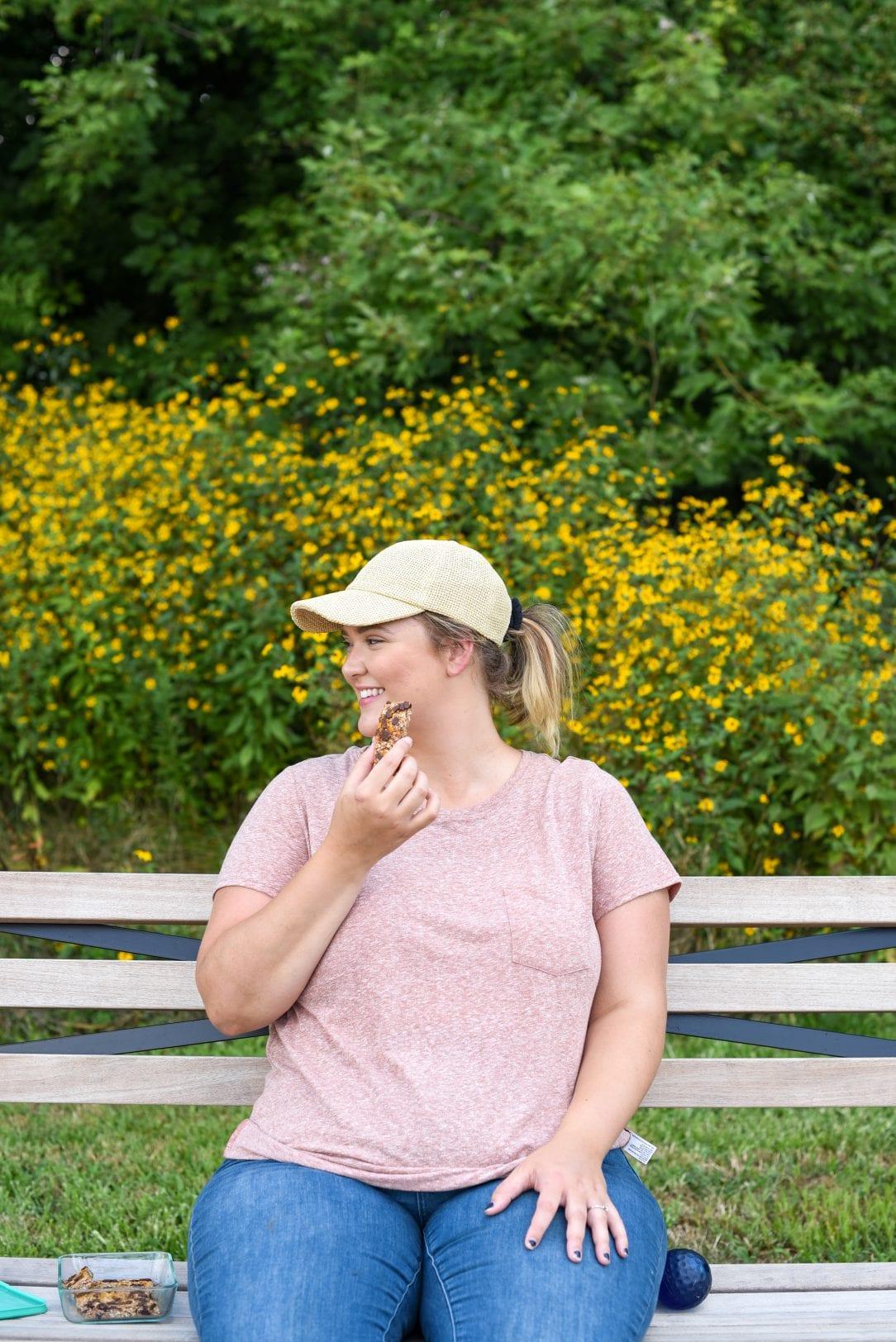 sitting on park bench eating granola bar