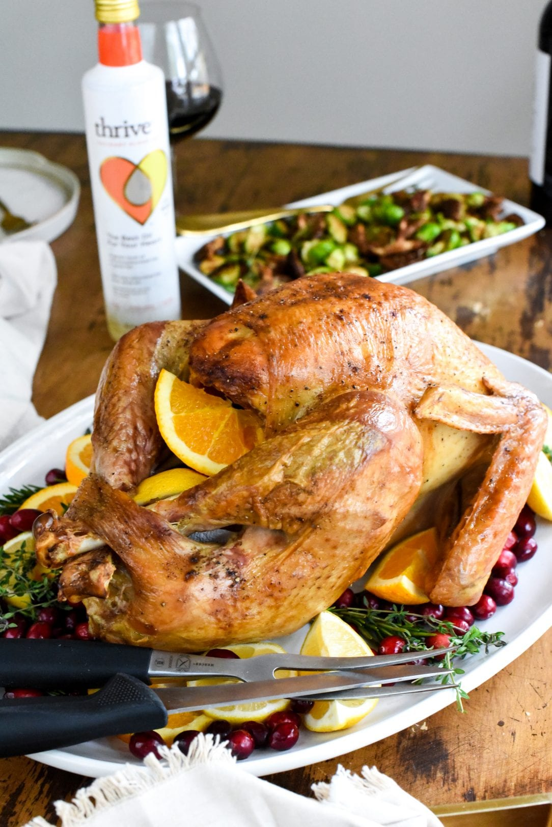 turkey on a serving dish with cranberries and orange slices