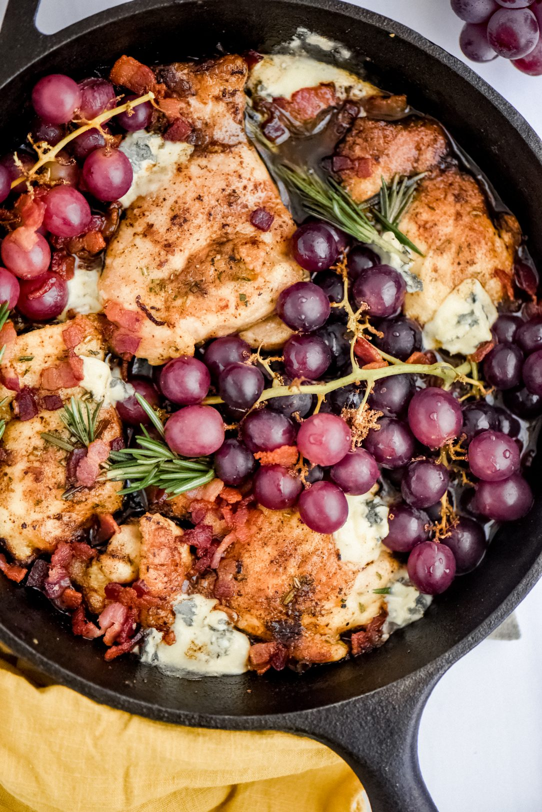 chicken thighs in skillet with grapes and blue cheese