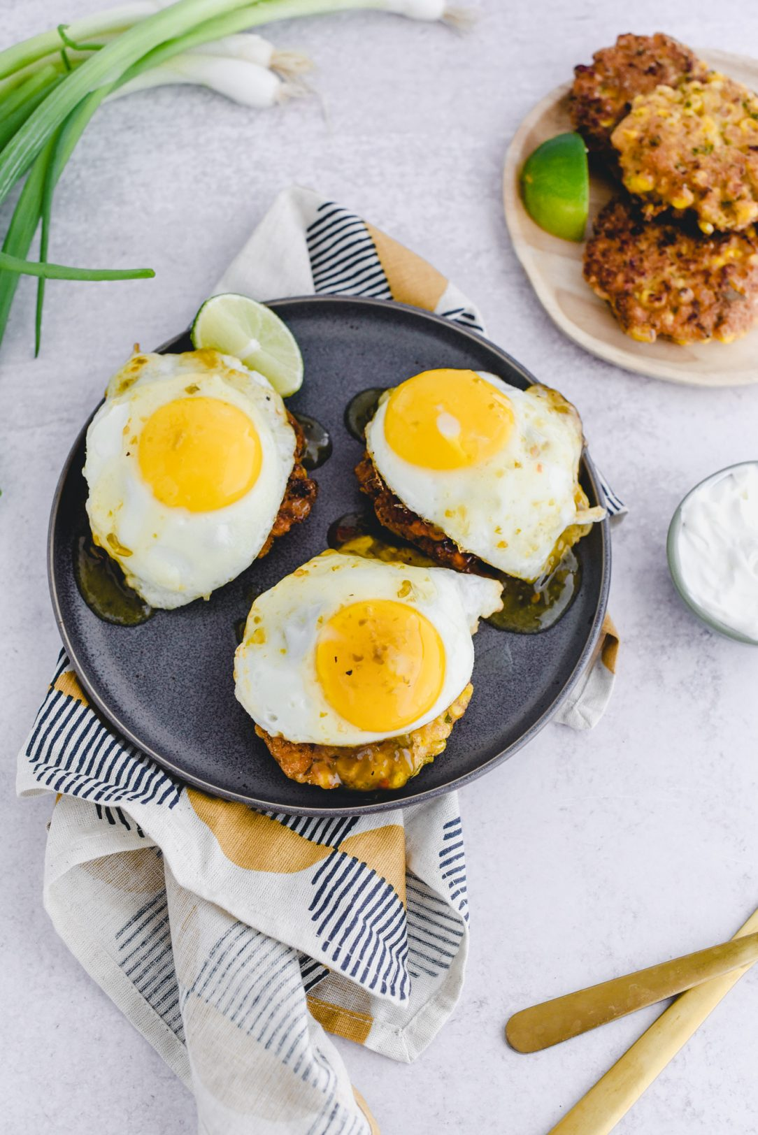 three corn fritters topped with eggs on a plate