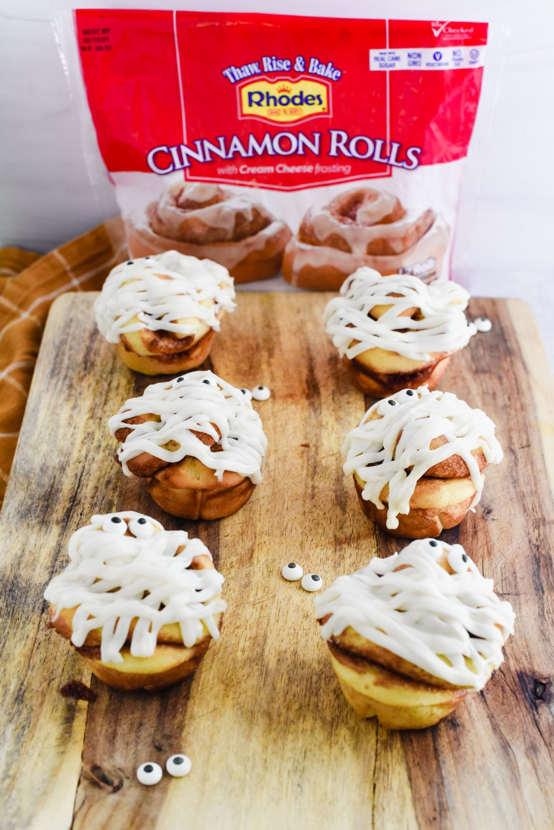 iced cinnamon rolls placed on cutting board