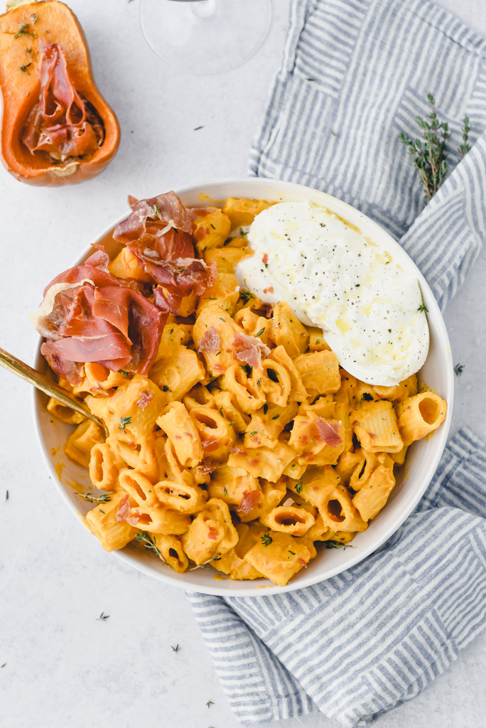 Creamy Honey Nut Squash Pasta in a shallow bowl with crispy prosciutto and burrata cheese on top.