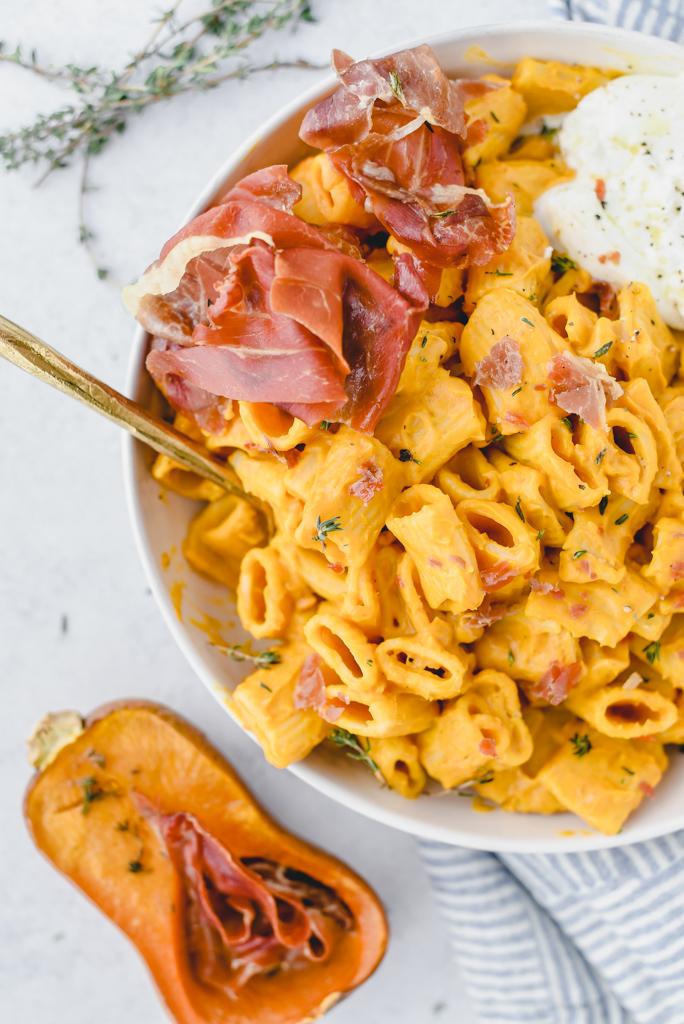 close Above shot of creamy honey nut squash pasta with Crispy prosciutto and burrata.