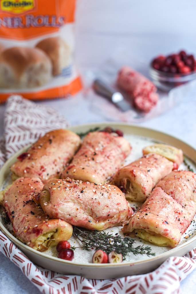 Leftover Turkey Rolls with Cranberry Butter piled on a plate with thyme and cranberries and a Rhodes Rolls bag in the background
