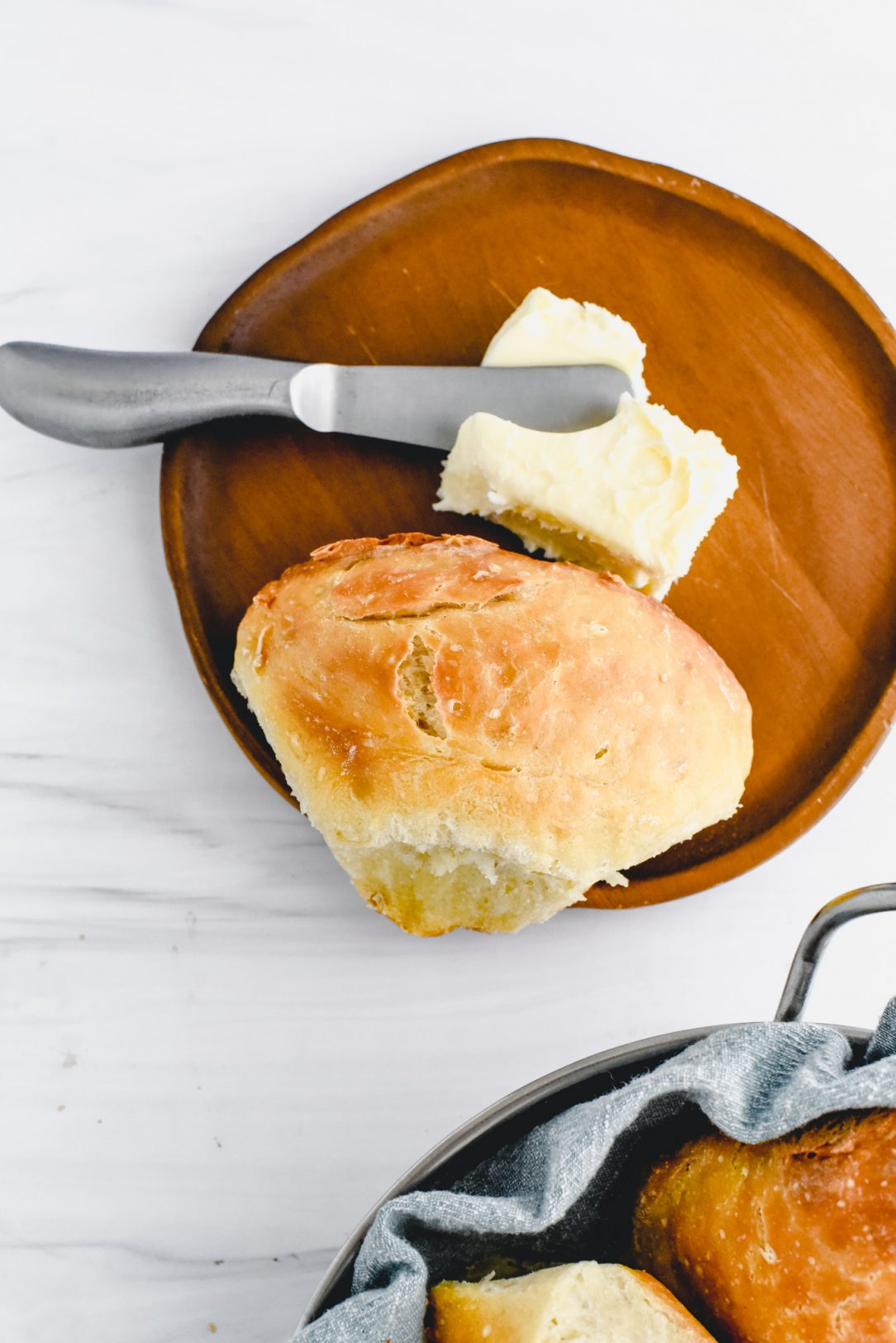baked roll on plate with butter and knife