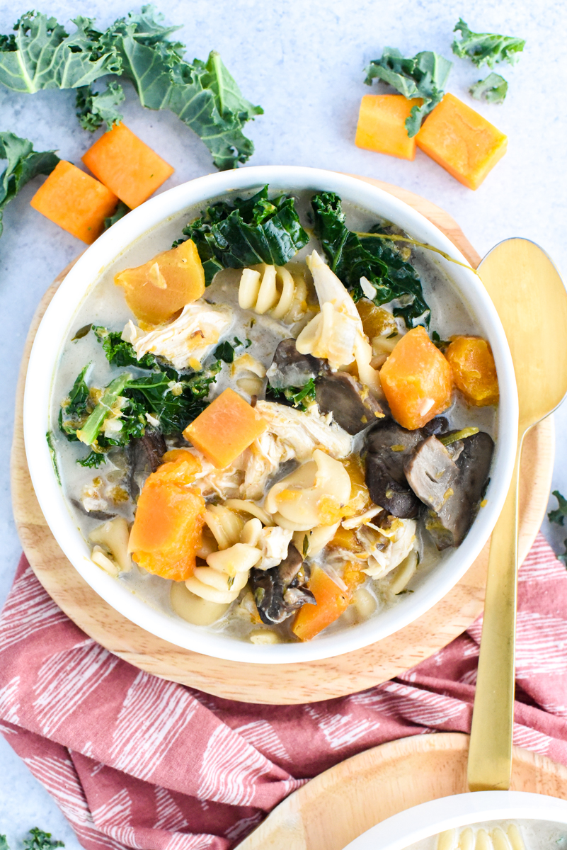 harvest hearty soup with kale and butternut squash in serving bowl