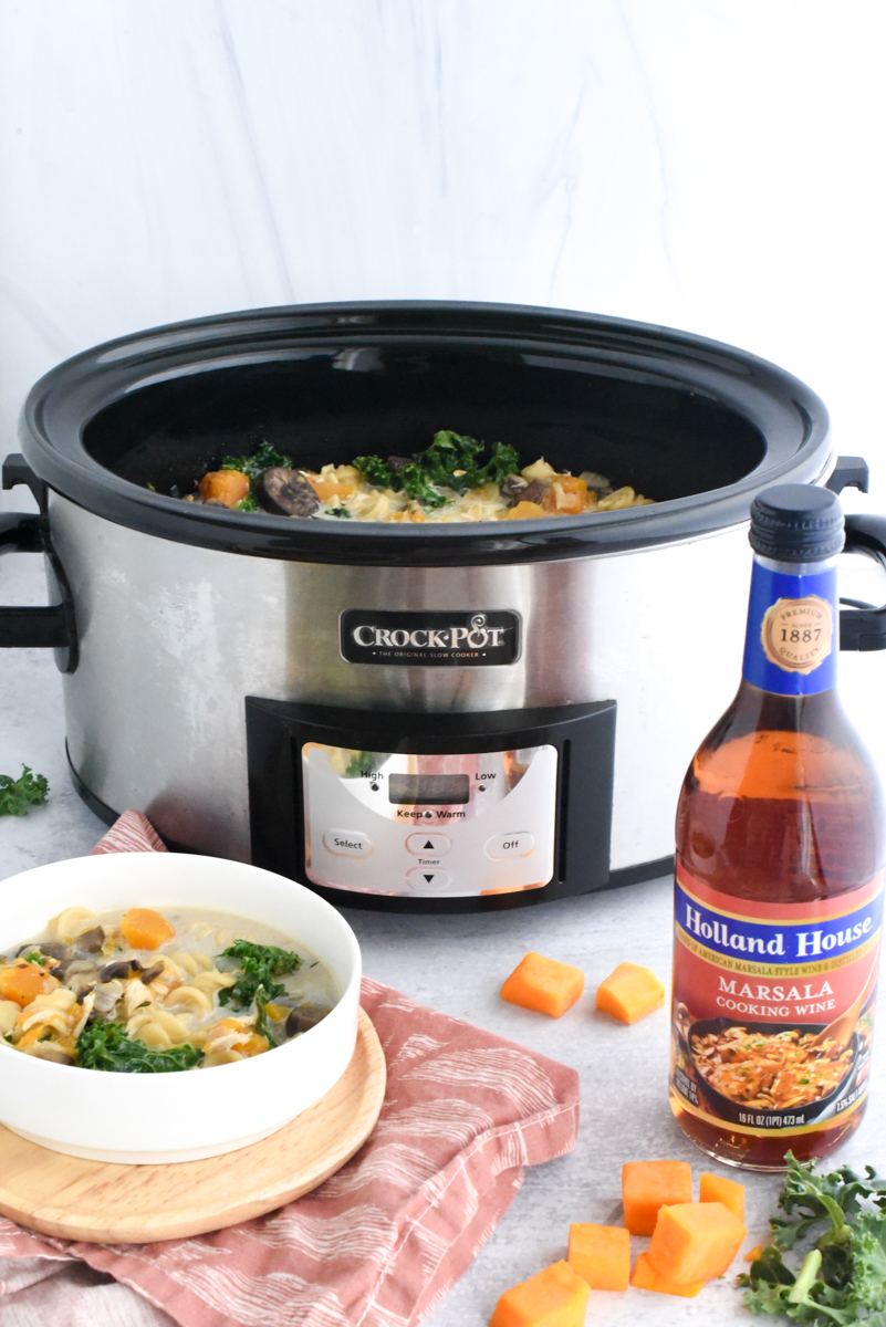 harvest hearty soup with kale and butternut squash in bowl and crockpot