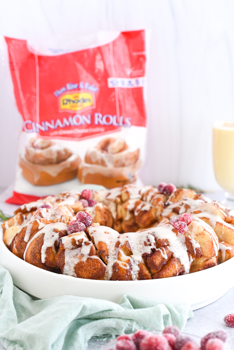 Monkey Bread in a ring with eggnog frosting drizzled over the top surrounded by sugared cranberries, rosemary and eggnog and a Rhodes Bread Bag in the background.