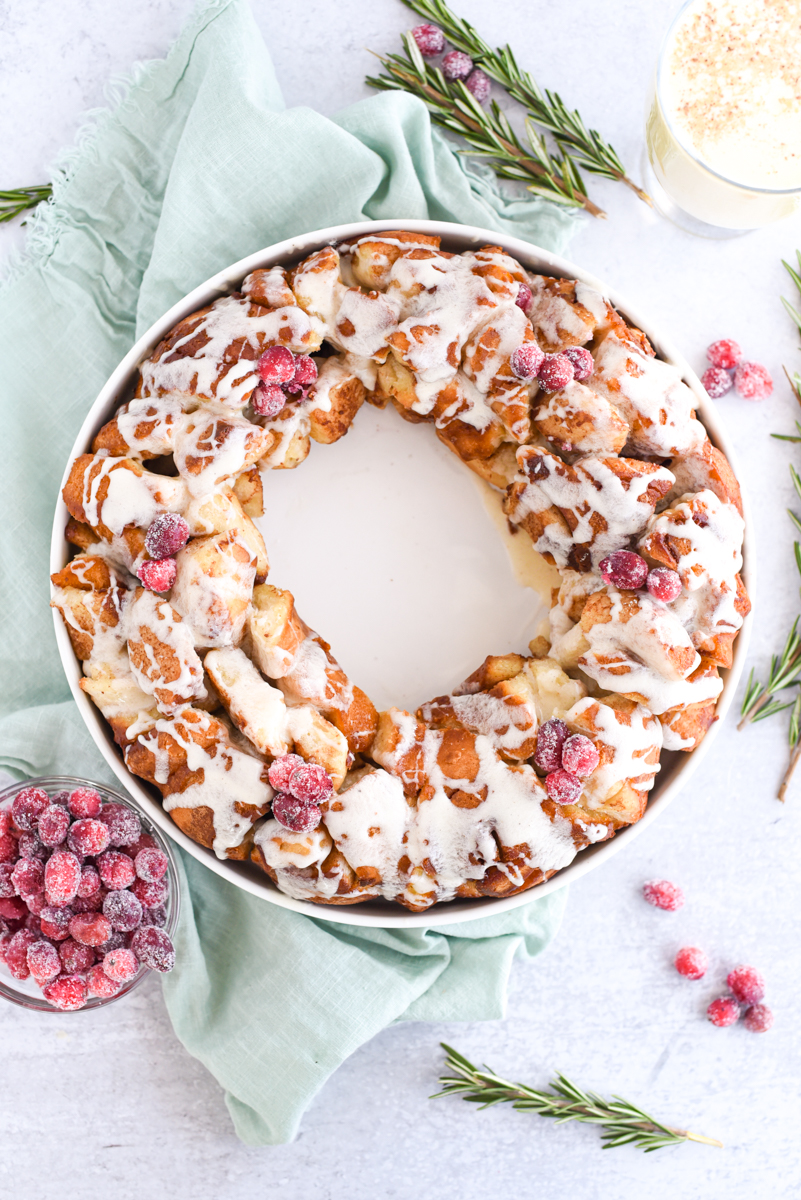 Monkey Bread in a ring with eggnog frosting drizzled over the top surrounded by sugared cranberries, rosemary and eggnog.