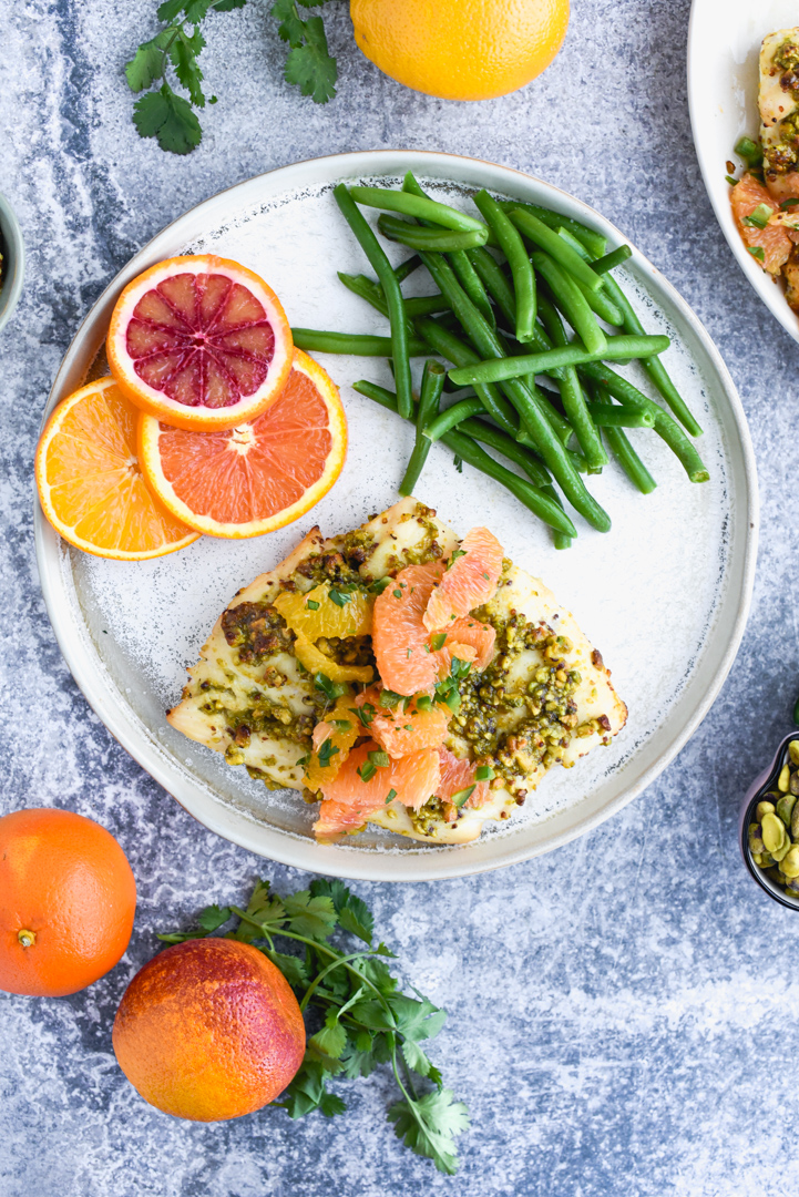 fish topped with oranges, pistachios and herbs on a plate with green beans and orange slices