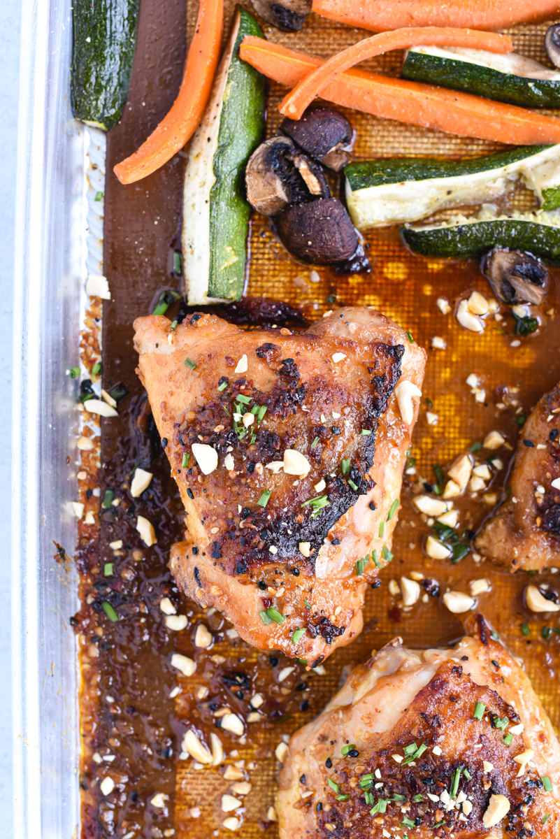 easy sheet pan peanut chicken on a roasting pan with vegetables