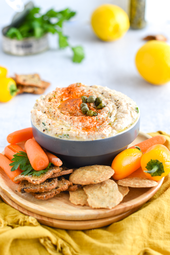 tuna spread in a serving bowl with crackers and vegetables on a plate