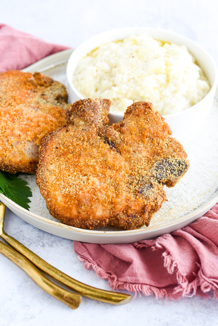 pork chops sitting on a plate with a side dish