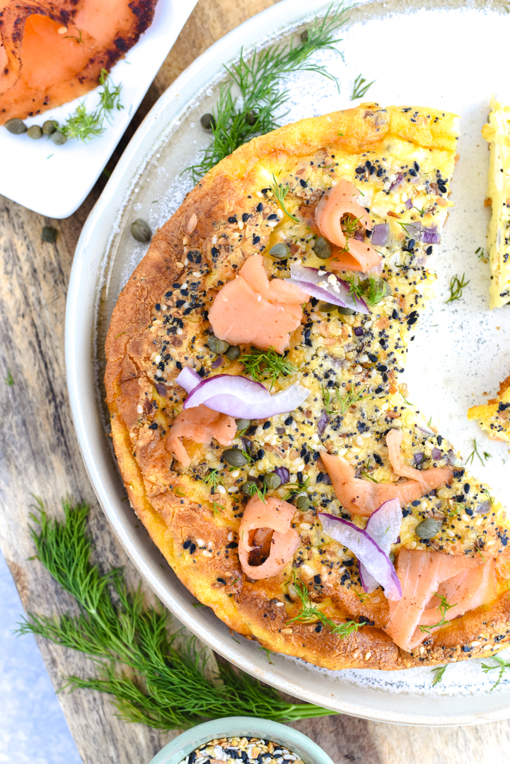 sliced quiche on a plate with salmon, onion, capers, and everything seasoning for garnish