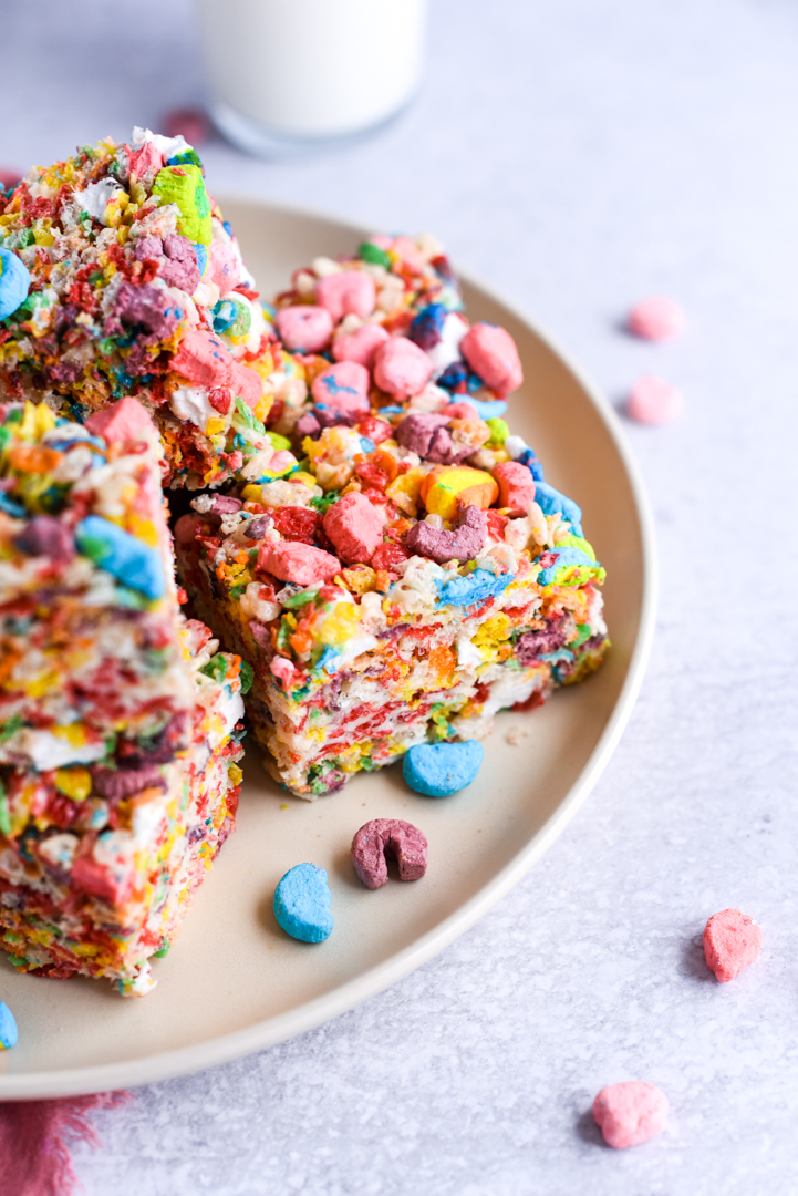 rainbow rice krispie treats stacked on a plate with a glass of milk in the background