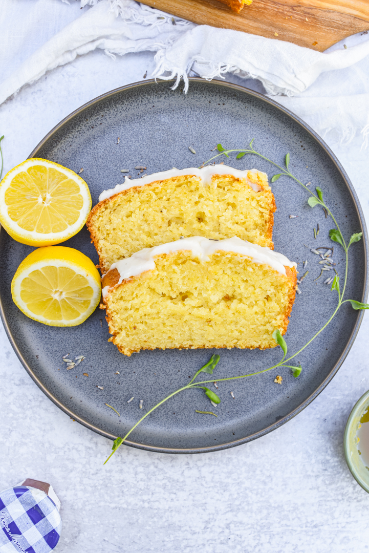 slices of Lavender Honey Soaked Lemon Cake on a plate with a sliced lemon and a sprig of rosemary